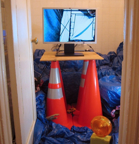 Elizabeth Riley Liberty Blue tarps, traffic cones, barricade light, plaster hand, <br>artificial pansies, toy taxi cabs, monitor and Liberty video