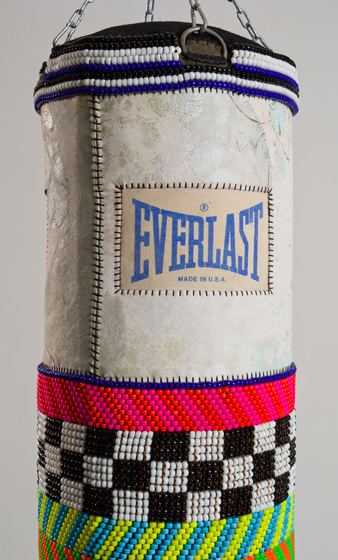 New York City Boy found canvas punching bag, recycled wool blanket, artist's own repurposed painting, glass beads, artificial sinew, tin jingles, nylon fringe