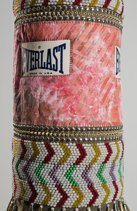 Homma found canvas punching bag, recycled wool blanket, artist's own repurposed painting, glass beads, steel studs, tin jingles, nylon fringe, artificial sinew