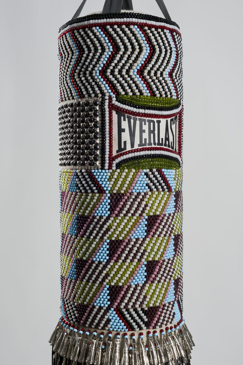 Hit That Perfect Beat found punching bag, repurposed wool blanket, glass beads, steel studs, tin jingles, nylon fringe, artificial sinew, steel chains