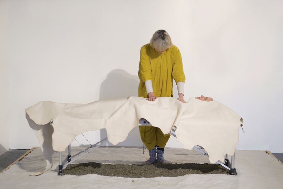 JEMILA MACEWAN a taming Performance with leather hide, massage table, soil, and cotton fabric.