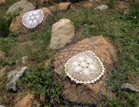 s i t e specific crocheted doilies stretched over found rocks