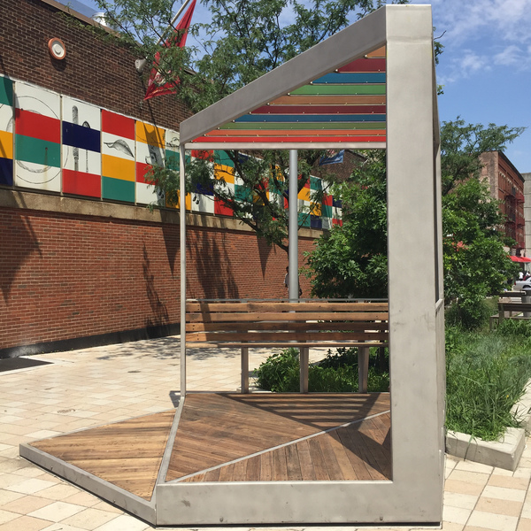 Austin Thomas Works Materials on the artwork include; stainless Steel with bead-blasted coating, reclaimed wood decking on the platforms, benches and seat backs, acrylic (3Form) paneled trellis and hardware.