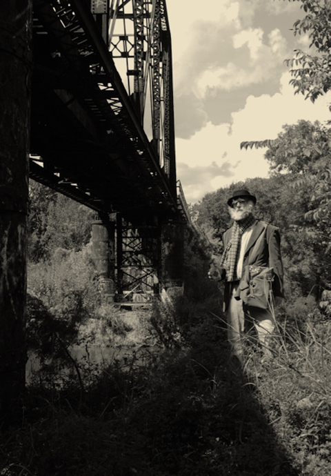 Dr. Graybones standing under train trestle