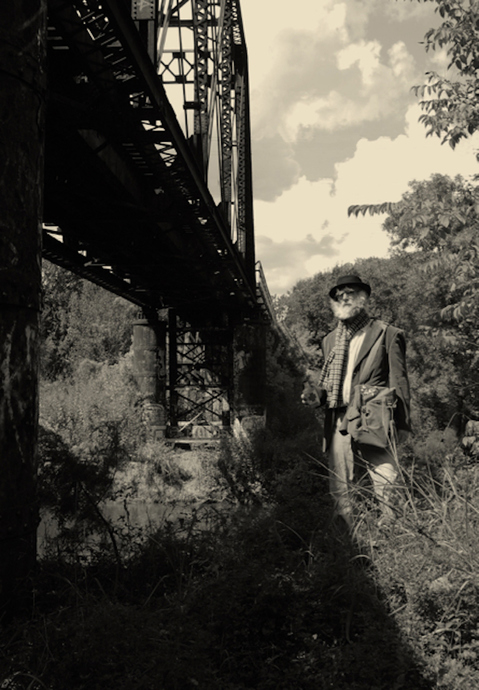 The World of Nomadic Fungi  Dr. Graybones standing under train trestle
