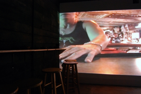 Cybele Lyle The Last Resort at Krowswork Gallery Video Projection, Wood Stools, Wood Bar, Mirrored Plexi, Dart Board, Red Light, Beer