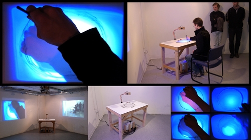 "Digital Files of Artists Eric Valosin, ""Circle,"" Installation size Variable, Table: 45"" x 40"" x 24.5,"" Drawings 12.5"" x 16,"" Performance and Installation using Custom Cyclical Rear Projection Table, Chair, Digital Projection, Charcoal, and Erasure on Vellum; Original Software and Hardware,2013."
