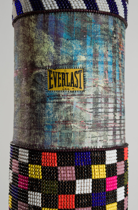 Gimme - Gimme, Shake – Shake  found vinyl punching bag, recycled wool blanket, artist's own repurposed painting, tin jingles, nylon fringe, artificial sinew