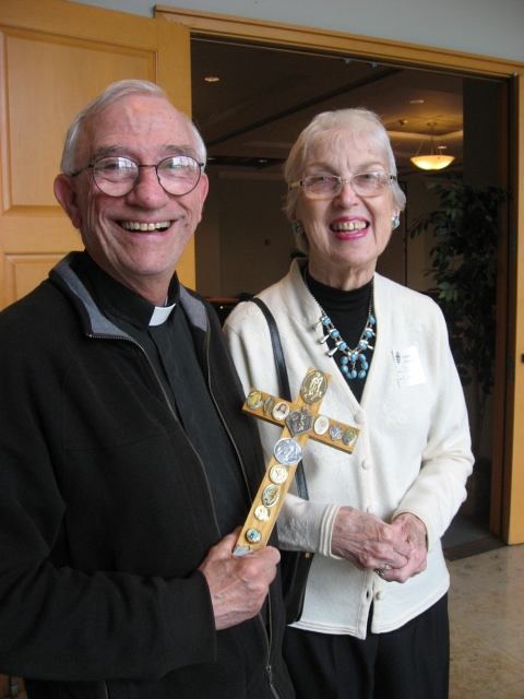 OLL Restoration Workshop Msgr Bradley and Jean Kubilus.  Msgr Edward Bradley was instrumental in this project.  He gathered the objects for us and gave us the biographies of the deceased priests.  In this picture, Jean is giving him a cross she made for him as a thank you gift.