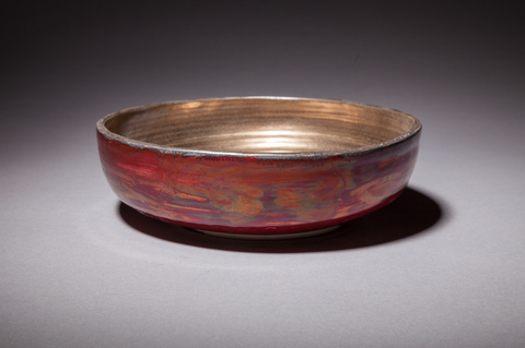Raku, Pit Fire and Luster ware Large plum red and gold bowl,
