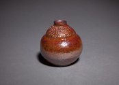 Wheel thrown and altered raku fired red stoneware clay with gold glaze sake bottle, small vase