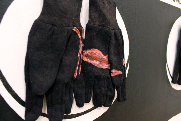 sculpture installation of six pairs of work gloves with acrylic paint, painted wall