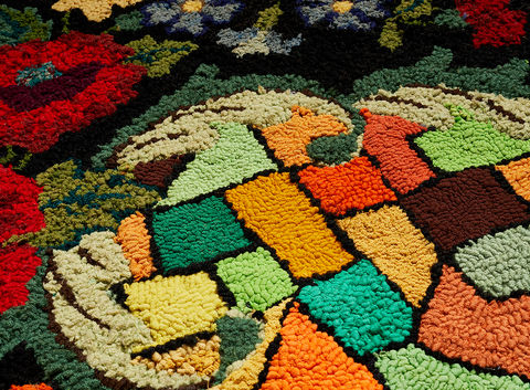 Venetia Dale piecing together collected and stitched together unfinished hooked rugs